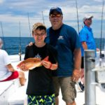 Young angler shows off his catch on a Destin party boat