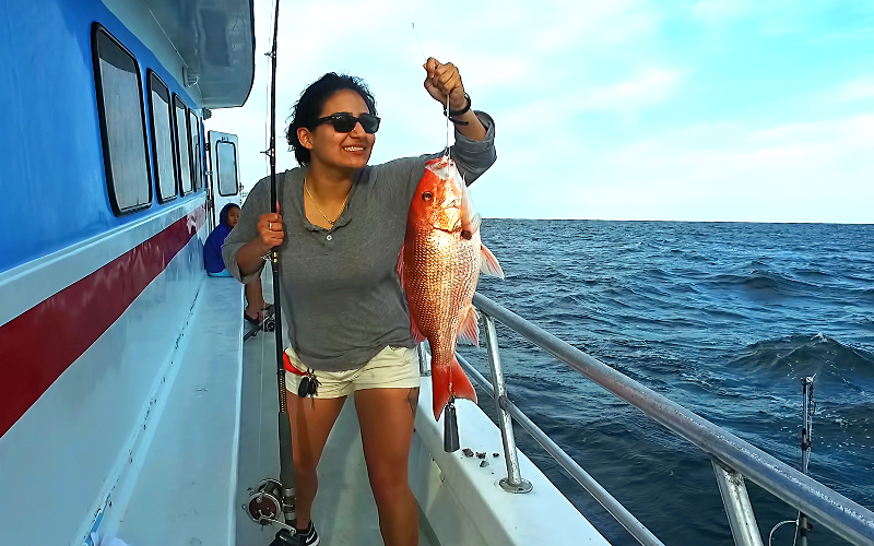 woman holding red snapper fish destin party boat
